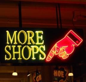 """Rótulo de neón que indica """"más tiendas"""" relativo a la psicología del consumo."""